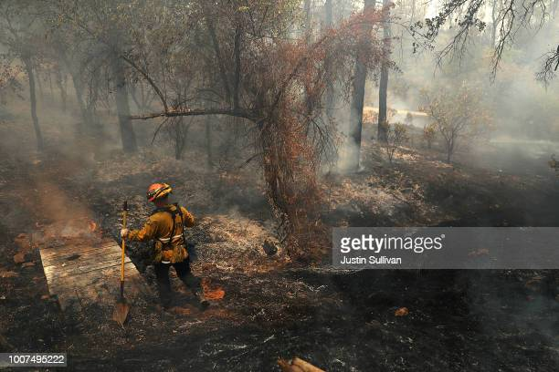 Los Angeles city firefighter walks through a charred field as he looks for hot spots after the Carr Fire burned through the area on July 29 2018 in...