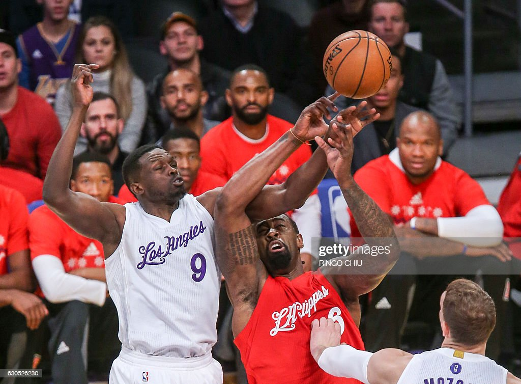 Los Angeles Clippers center DeAndre Jordan (#6) and Los Angeles Lakers forward Luol Deng (9) flight for a ball during their NBA game at Staples Center in Los Angeles, California on December 25, 2016