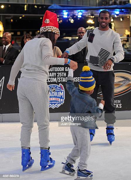 Los Angeles Clippers' Chris Paul watches his wife and son ice skate during AEG's Season of Giving event at Nokia Plaza LA Live on December 19 2013 in...