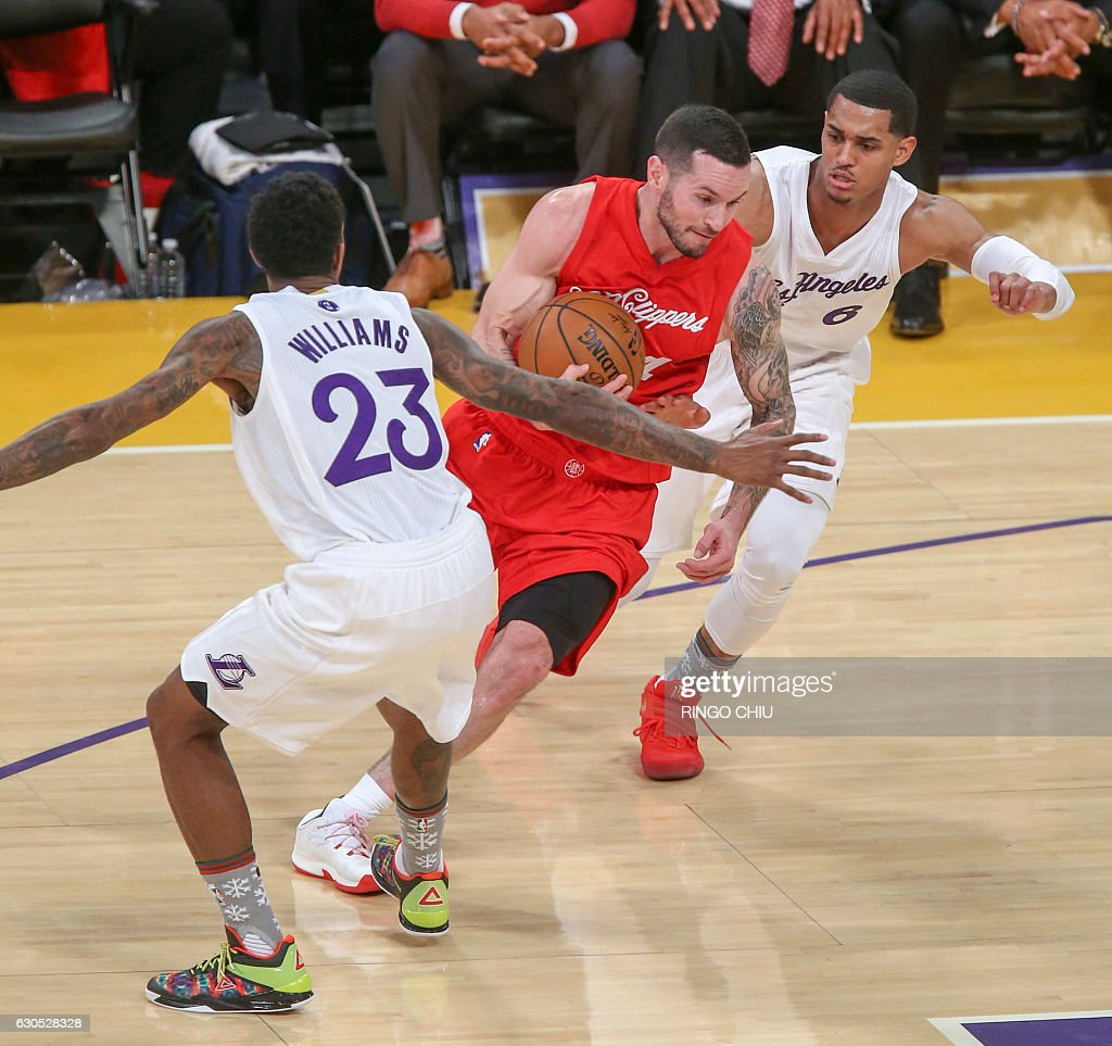 Los Angeles Clippers guard J.J. Redick (#4) drives between Los Angeles Lakers guards Jordan Clarkson (#6) and Louis Williams (23) during their NBA game at Staples Center in Los Angeles, California on December 25, 2016. / AFP / RINGO