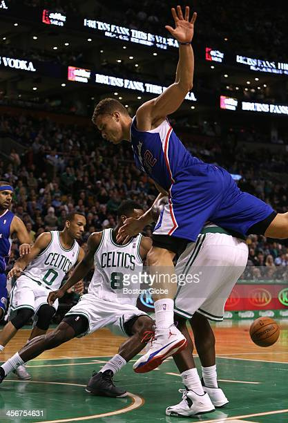 Los Angeles Clippers power forward Blake Griffin falls over the back of Boston Celtics power forward Brandon Bass after a missed basket in the second...