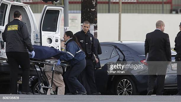 CA FEBRUARY 9 2016 Los Angeles County coroner investigators remove the body from a bullet riddled car with an Uber sticker near the intersection of...