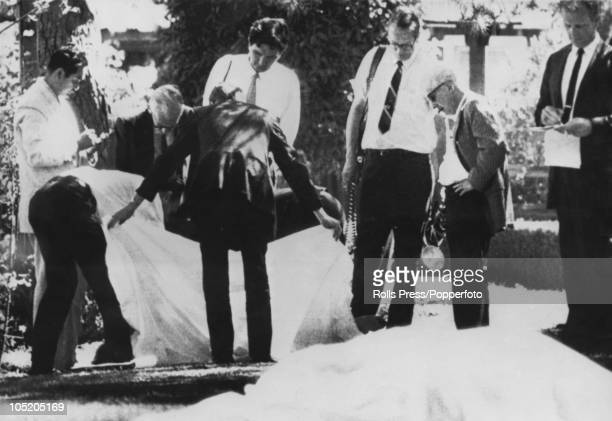 Los Angeles County Coroner Thomas Noguchi takes notes as his assistants remove the sheet from a murder victim on the lawn of Roman Polanski's LA home...