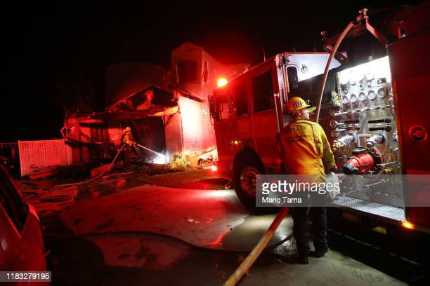 Los Angeles County Fire Department firefighters work at a home destroyed by the Tick Fire on October 24 2019 in Canyon Country California The fire...