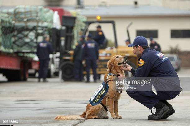 Los Angeles County Fire Department urban search and rescue dog Baxter and handler Gary Durian prepare for deployment as other team members load US...
