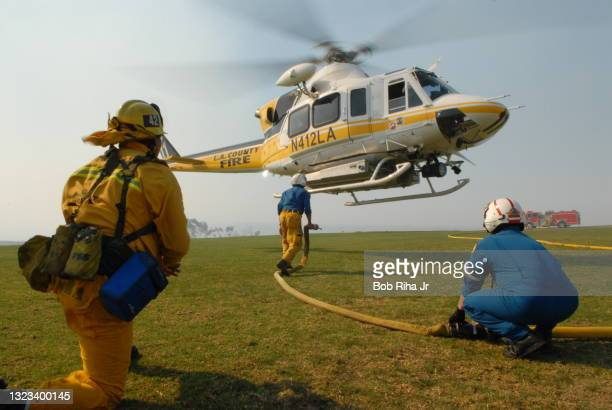 Los Angeles County Fire fighters prepare to reload firefighting helicopter with water on the lawn of Pepperdine University during wildland fires,...