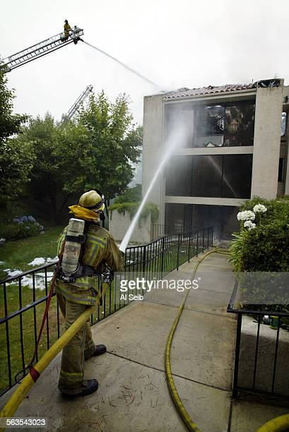 HILLS CA Los Angeles County firefighter Jon Ferguson from Station 65 and an LA County Fire Department ladder pour water on the stubborn fire into a...