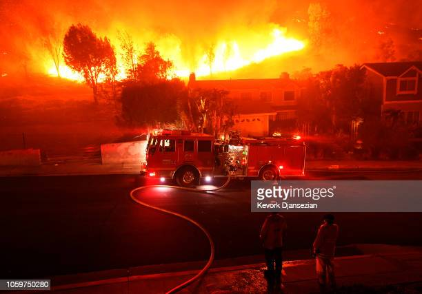 Los Angeles County firefighter looks on as the out of control Woolsey Fire explodes behind a house in the West Hills neighborhood on November 9 2018...