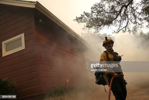 Los Angeles County firefighter monitors approching flames near a building as an out of control wildfire moves through the area on October 9 2017 in...