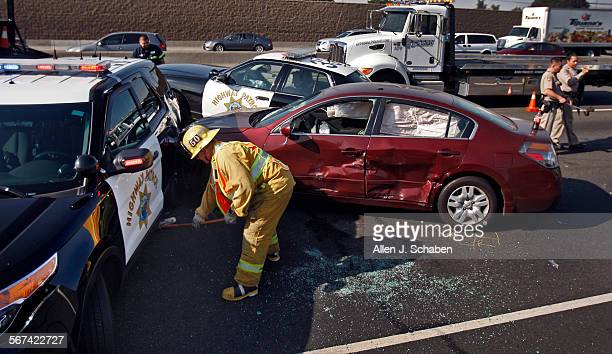 Los Angeles County firefighter/paramedic cleans up the scene as California Highway Patrol officers investigate the scene where two California Highway...