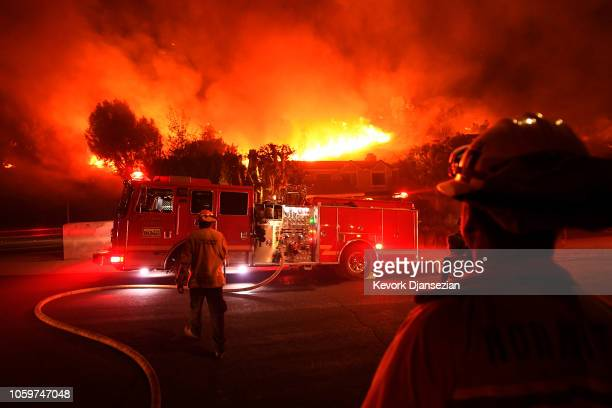 Los Angeles County firefighters look on as the out of control Woolsey Fire explodes behind a house in the West Hills neighborhood on November 9 2018...