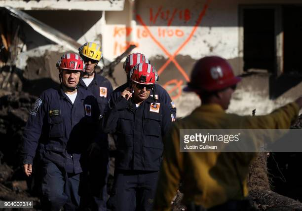 Los Angeles County firefighters prepare to investigate a home after a cadaver dog alerted on a pile of debris from a mudslide on January 11 2018 in...