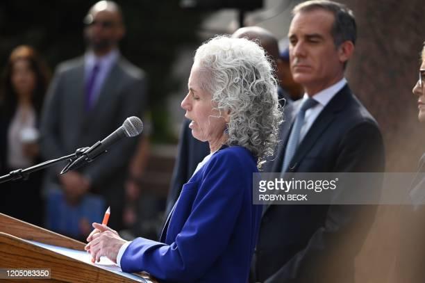 Los Angeles County Public Health director Barbara Ferrer speaks as Los Angeles Mayor Eric Garcetti looks on at an Los Angeles County Health...