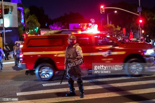 A Los Angeles County Sheriff officer takes position as people protesting over the lack of criminal charges in the police killing of Breonna Taylor...
