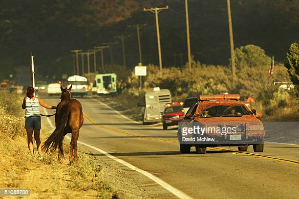 Los Angeles County Sheriffs car covered with red fire retardant passes a woman leading her horse to safety at the Crown Fire on July 20 2004 near...