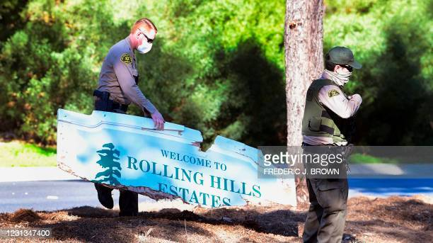 """Los Angeles County sheriffs department officer carries a broken """"Welcome to Rolling Hills Estates"""" sign destroyed from the vehicle drven by golfer..."""