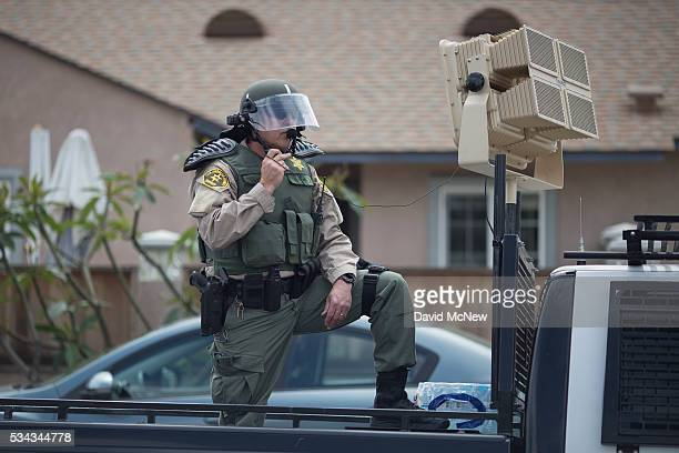 Los Angeles County Sheriffs deputy in riot gear stands ready to use a sound cannon or Long Range Acoustic Device against protesters near a campaign...
