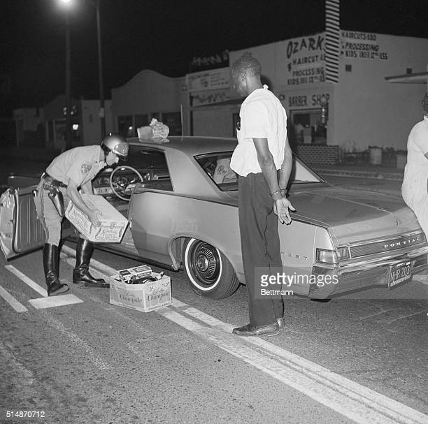 Los Angeles County Sheriffs search a car during the Watts Riots finding a case of vodka while the car's driver stands handcuffed nearby