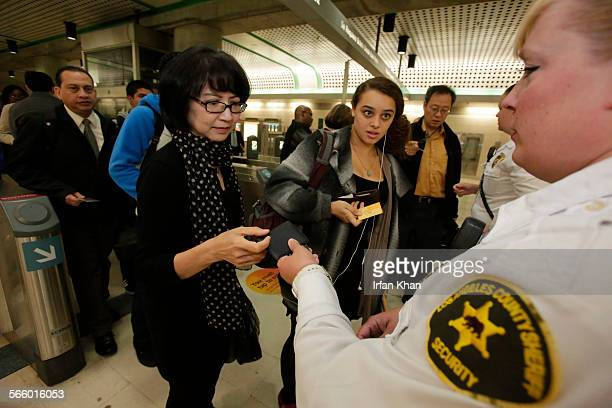 Los Angeles County Sheriff's Security Assistant/FareInspectors April Ramirez checks commuters TAP cards for payment of subway fare at Civic...