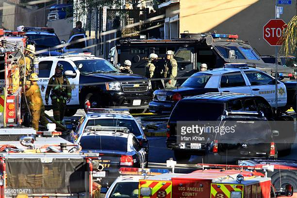 Los Angeles county Sheriff's SWAT team and fire fighters clog the street leading to a house where a man barricaded himself Man allegedly fired a...