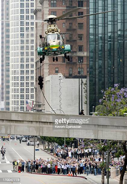 Los Angeles County Sheriff's SWAT team member rappels down from a low flying law enforcement helicopter during a drill involving a response to...