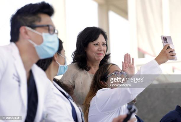 Los Angeles County Supervisor Hilda Solis poses for a selfie with health officials and essential workers at an event to observe the reopening of...
