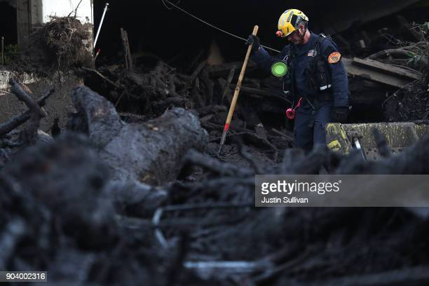 Los Angeles County urban search and rescue worker searches a pile of debris for victims of a mudslide on January 11 2018 in Montecito California 17...