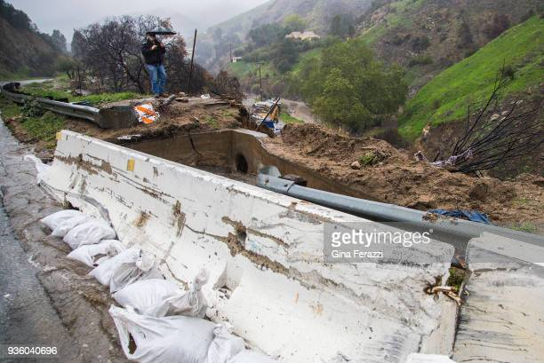 Los Angeles county worker Brian Miller inspects the drainage flow on a culvert in the 8300 block of La Tuna Canyon as heavy rains caused street...