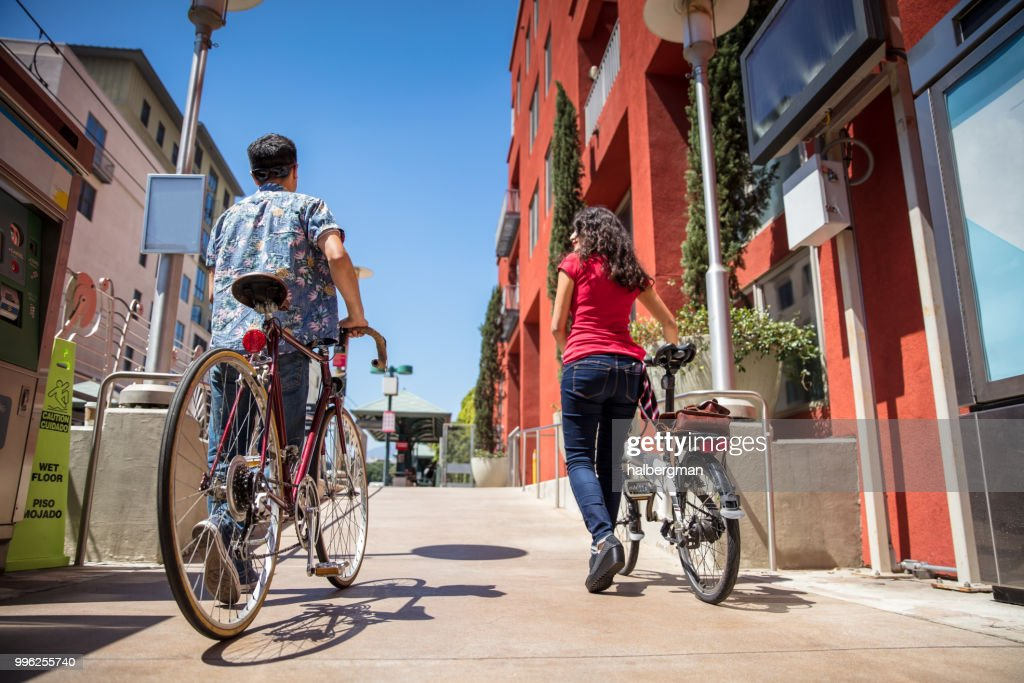 Los Angeles Couple Pushing Bicycles Onto Light Rail Platform : Stock Photo