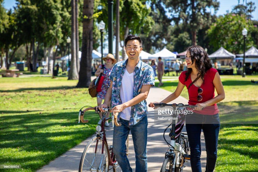 Los Angeles Couple Wheeling Bikes Through Park Durning Farmer's Market : Stock Photo