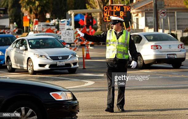 Los Angeles Department of Transportation traffic officer Rosser directs traffic at the intersection of Coldwater Canyon Avenue and Ventura Boulevard...