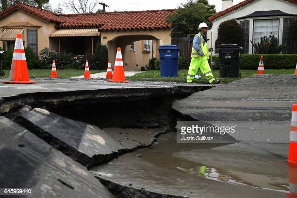 Los Angeles Department of Water and Power worker walks by a massive sinkhole on West Boulevard on February 27 2017 in Los Angeles California...