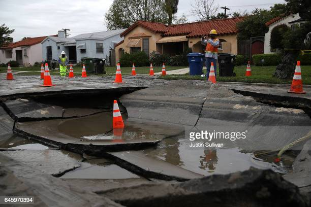 Los Angeles Department of Water and Power workers inspect a massive sinkhole on West Boulevard on February 27 2017 in Los Angeles California...