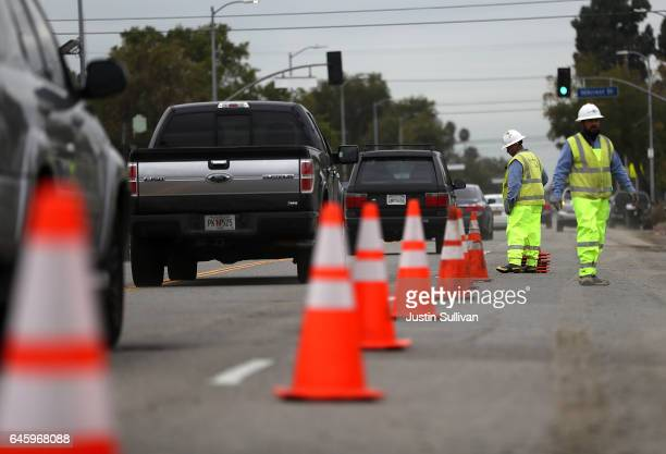 Los Angeles Department of Water and Power workers set up raod cones to divert traffic away from a massive sinkhole on West Boulevard on February 27...
