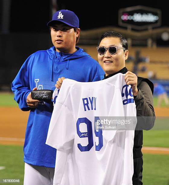 Los Angeles Dodger pitcher HyunJin Ryu presents Korean pop superstar PSY with his jersey following the game between the Los Angeles Dodgers and...