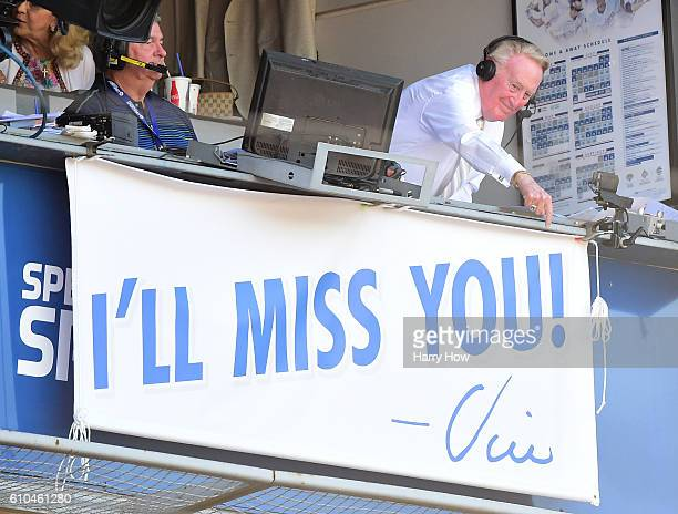 Los Angeles Dodgers announcer Vin Scully points to the sign as he receives an applause during the seventh inning stretch against the Colorado Rockies...