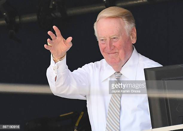 Los Angeles Dodgers broadcaster Vin Scully acknowledges the umpired crew before the start of the game against the Chicago Cubs at Dodger Stadium on...