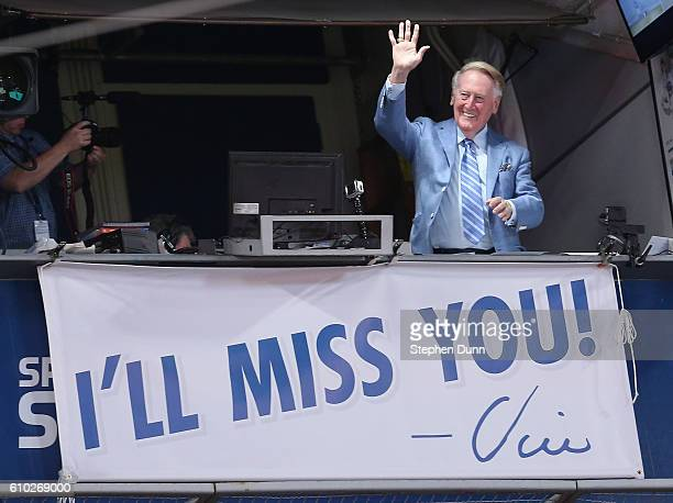 Los Angeles Dodgers broadcaster Vin Scully waves to the crowd after leading in the singing of Take Me Out to the Ball Game during the seventh inning...