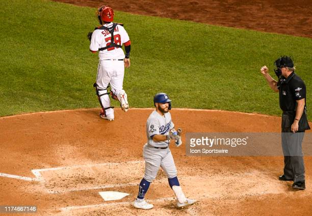 Los Angeles Dodgers catcher Russell Martin and Washington Nationals catcher Kurt Suzuki walk back to their dugouts after home plate umpire Ted...