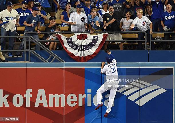Los Angeles Dodgers Center field Joc Pederson scales the outfield wall to try and catch a home run ball by Chicago Cubs First base Anthony Rizzo in...