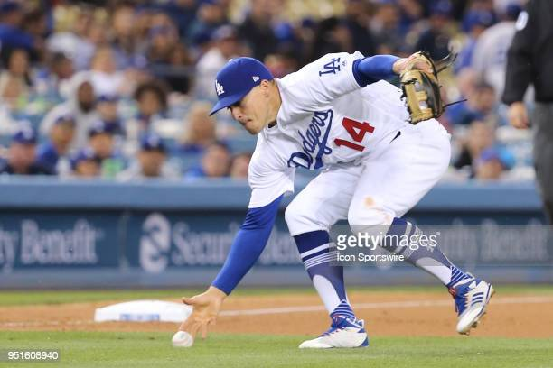 Los Angeles Dodgers center fielder Enrique Hernandez barehands a slow grounder to third in the game between the Miami Marlins and Los Angeles Dodgers...