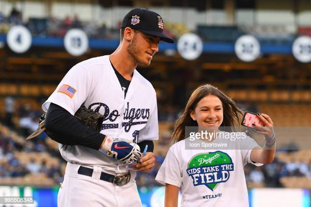 Los Angeles Dodgers first baseman Cody Bellinger takes a selfie with a young fan before a MLB game between the Pittsburgh Pirates and the Los Angeles...