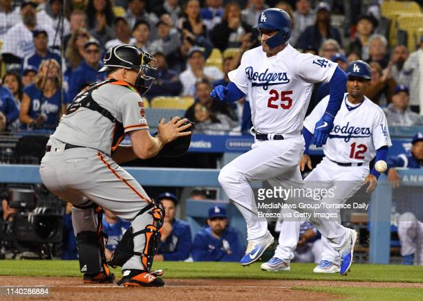 Los Angeles Dodgers first baseman David Freese beats the tag at home by San Francisco Giants catcher Erik Kratz in the first inning at Dodger Stadium...