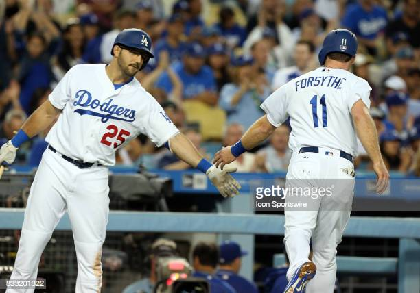 Los Angeles Dodgers infielder Rob Segedin congratulates Los Angeles Dodgers second baseman Logan Forsythe after Forsythe scores on a wild pitch...
