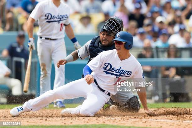 Los Angeles Dodgers left fielder Enrique Hernandez slides safely onto home plate before being tagged by San Diego Padres catcher Hector Sanchez...