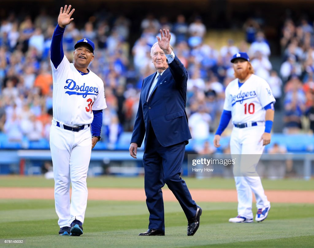 Los Angeles Dodgers manager Dave Roberts and announcer Vin Scully wave to fans during his induction into the Los Angeles Dodgers Ring of Honor at Dodger Stadium on May 3, 2017 in Los Angeles, California.