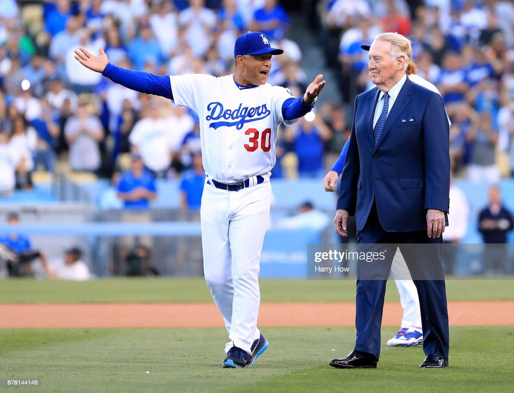 Los Angeles Dodgers manager Dave Roberts laughs as he leads announcer Vin Scully to the field during his induction into the Los Angeles Dodgers Ring of Honor at Dodger Stadium on May 3, 2017 in Los Angeles, California.