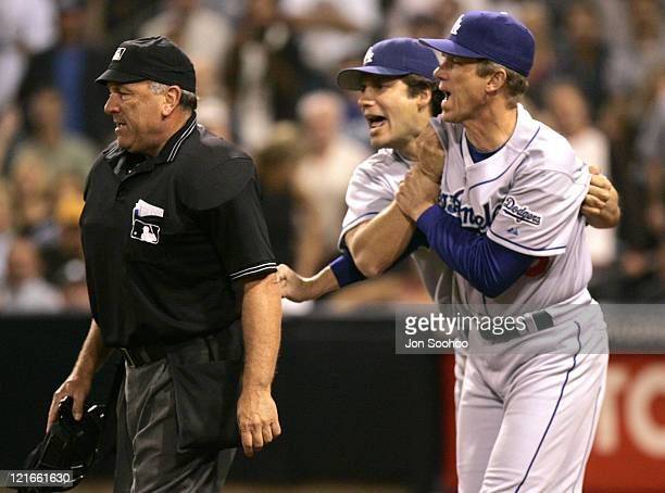 Los Angeles Dodgers manager Jim Tracy [R] holds back Dodger Robin Ventura from going after umpire Ed Montague during game vs San Diego Padres...