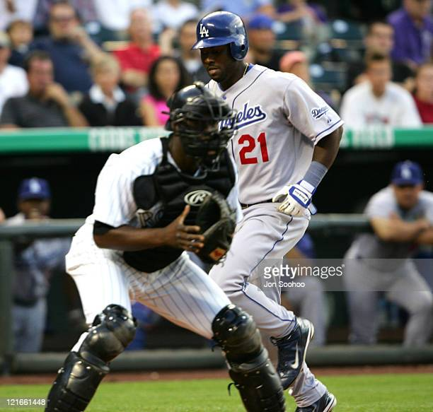 Los Angeles Dodgers Milton Bradley scores ahead of the tag of Colorado Rockies Charles Johnson in the third inning at Coors Field in Denver Colorado...