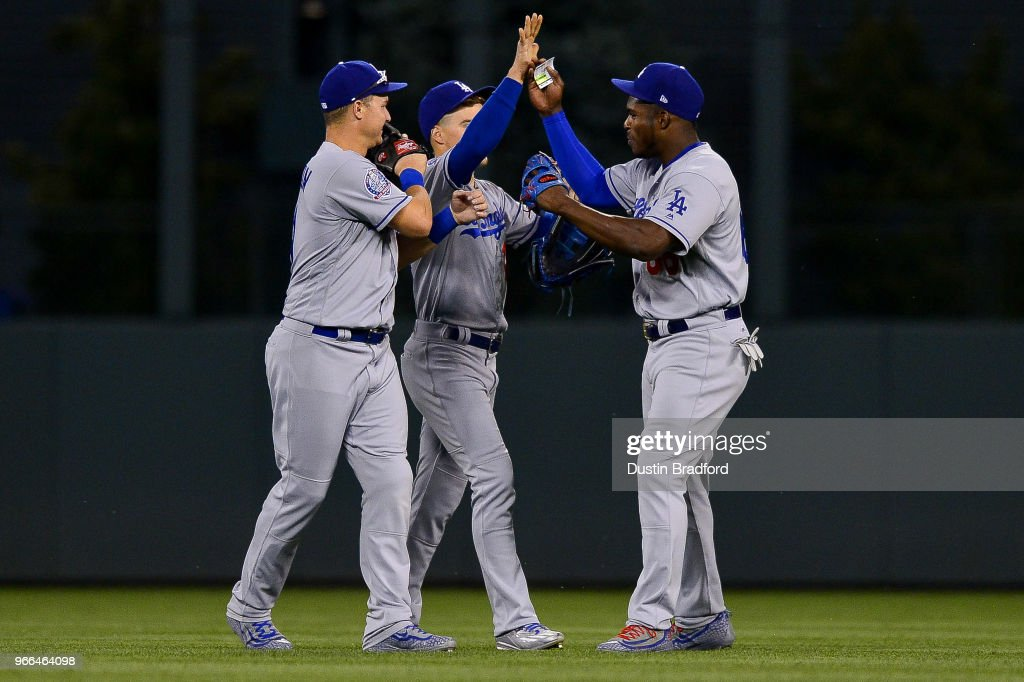 Los Angeles Dodgers outfielders, from left, Joc Pederson #31, Enrique Hernandez #14, and Yasiel Puig #66 celebrate after a 12-4 win over the Colorado Rockies at Coors Field on June 2, 2018 in Denver, Colorado.